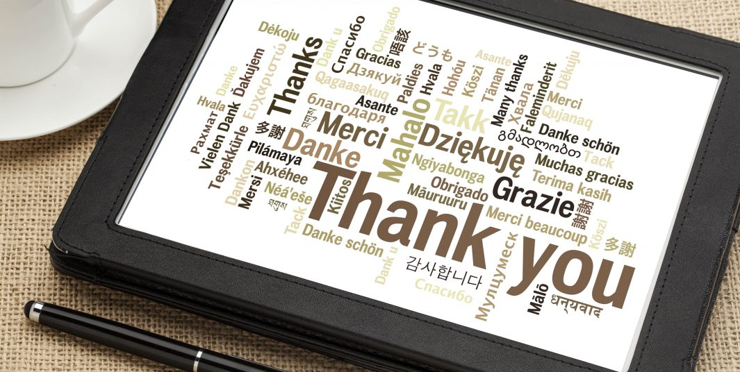 thank you in different languages - word cloud on a  digital tablet with a cup of coffee